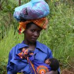 african woman carrying baby